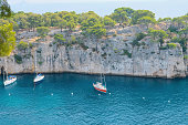 turquoise sea water rocky cliffs boats
