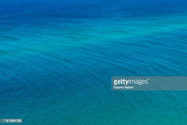 turquoise sea with gentle waves, abstract nature background - north stradbroke island, queensland - pacific ocean stock pictures, royalty-free photos & images