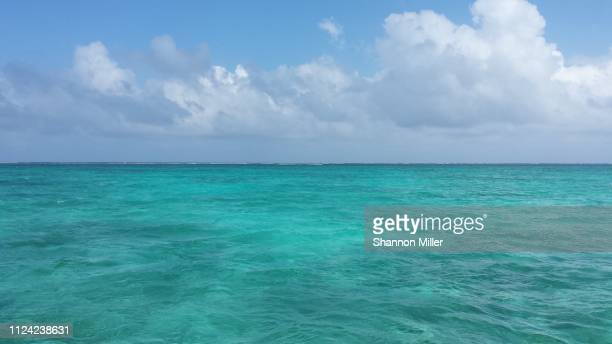 turquoise water of belize with billowy cloud - belize stock pictures, royalty-free photos & images