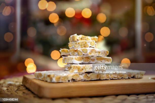 turrón. almond nougat on wooden board in front of christmas tree - nougat stock pictures, royalty-free photos & images