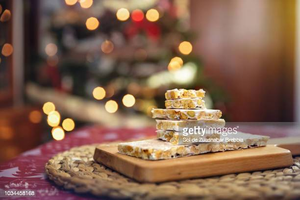 Turrón, Almond nougat, on wooden board next to the Christmas tree