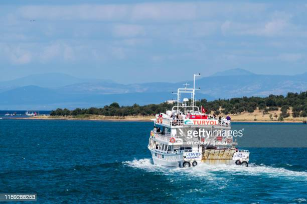 turyol which belongs to the transport company is a ferry carrying passengers and vehicles from ayvalık to mytilene in turkey. in the background is the island of lesbos - mytilene stock photos and pictures
