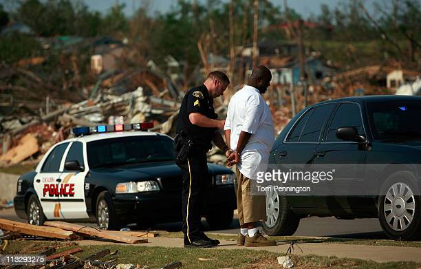 Tuscaloosa police officer handcuffs a suspected looter in a destroyed neighborhood on April 30, 2011 in Tuscaloosa, Alabama. Alabama, the hardest-hit...