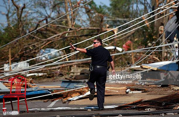 Tuscaloosa police officer signals a fellow officer while searching for a suspected looter in a destroyed neighborhood on April 30, 2011 in...