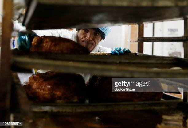 Tuscan Brands worker reaches in to grab a turkey breast as he and others prepare food for boxed Thanksgiving dinners in Lawrence MA on Nov 22 2018...