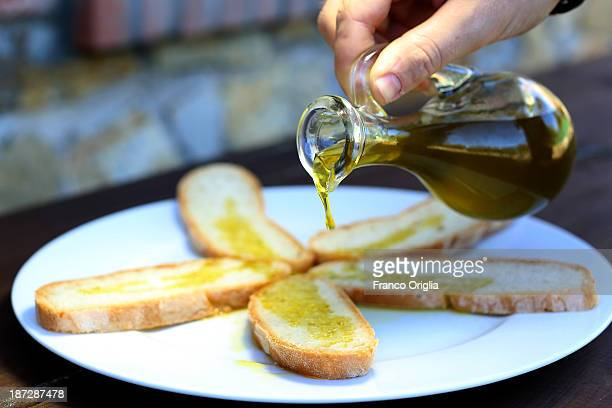 Tuscan bread is topped with fresh olive oil for a taste during the harvesting of olives at the Castello La Leccia estate on November 7 2013 in...