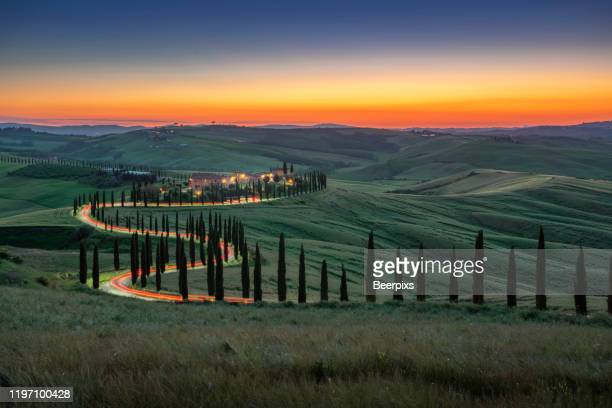 tuscany, crete senesi rural sunset landscape. countryside farm, cypresses trees, green field, sun light and cloud. italy. - cipresso foto e immagini stock