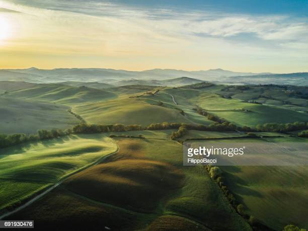 tuscany landscape at sunrise with low fog - campo foto e immagini stock