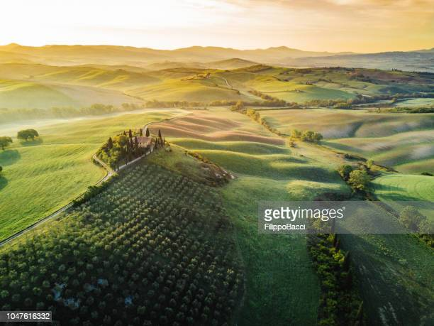 tuscany's valley in val d'orcia at sunrise from aerial point of view - toscana foto e immagini stock
