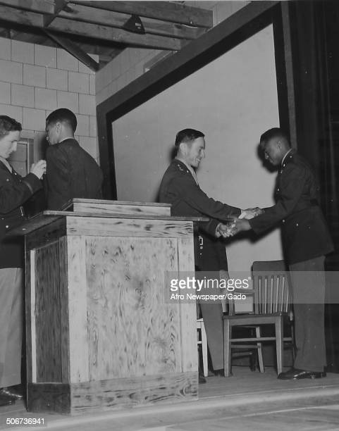 Tuskegee Airman shaking hands and receiving wings during a graduation ceremony and World War 2, 1942.