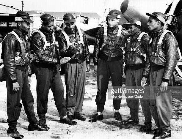Tuskegee Airmen African American pilots talking over Big Ship manoeuvres at Tuskegee Army Air Field with airplanes in the background Tuskegee Alabama...