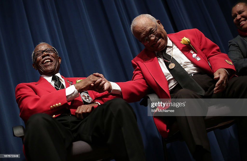 Tuskegee Airmen Major Anderson (L) and William Fauntroy (R) joke with each other during a ceremony commemorating Veterans Day and honoring the Tuskegee Airmen November 11, 2013 in Washington, DC. The ceremony was held at the African American Civil War Museum on the day that World War I ended 95 years ago, the date the United States honors all of its military veterans.