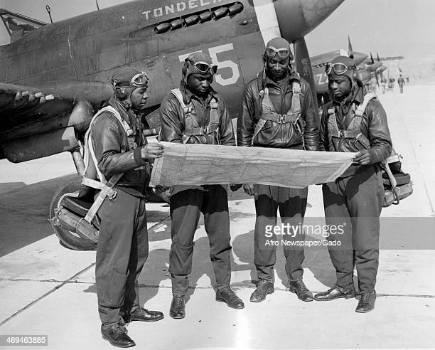 Tuskegee Airmen Pearlee E Saunders Leroy Bowman William M Gordon and Lloyd Singletary studying maps before flying a fighter plane at Tuskegee Army...