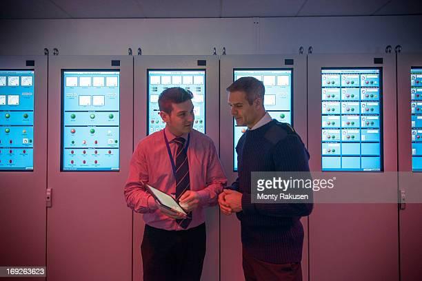 Tutor advising student in ship's engine room simulator