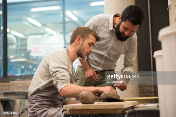 Tutor and student in art studio using pottery wheel