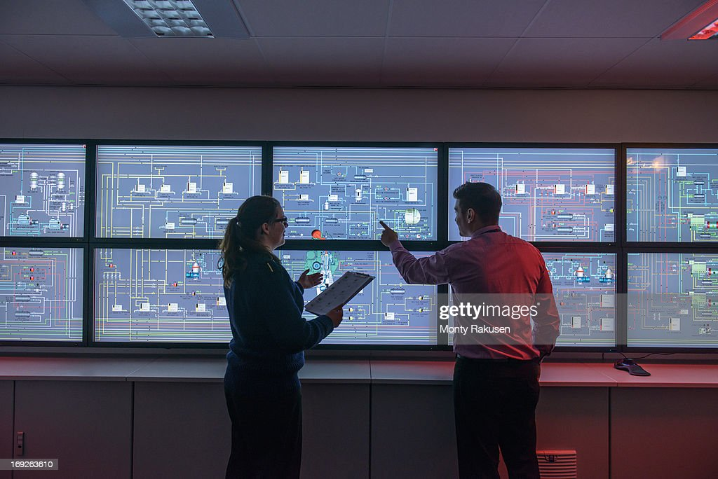 Tutor and student in front of monitors in ship's engine room simulator : Stock Photo