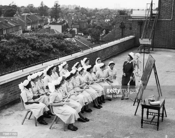 Tutor Margaret Young uses a skeleton to help her give an anatomy class to a group of student nurses on the roof of St James' Hospital Balham London...