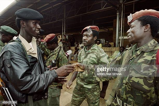 A Tutsi soldier from the Rwandan Patriotic Front shakes hands with Hutu soldiers from the former Rwandan army on August 18 1994 in a reconciliation...