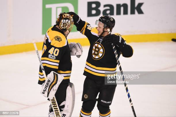 Tuukka Rask and David Pastrnak of the Boston Bruins celebrate a win against the New York Islanders at the TD Garden on December 9 2017 in Boston...