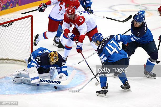 Tuukka Rask of Finland makes a save against Valeri Nichushkin of Russia as Antti Pihlstrom and Lasse Kukkonen of Finland defend during the Men's Ice...