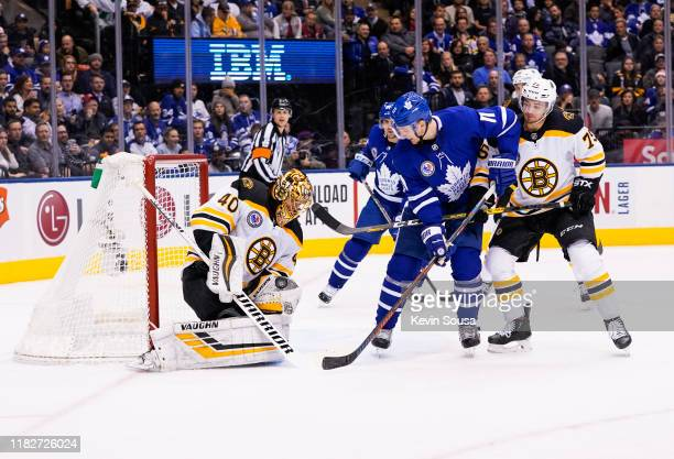 Tuukka Rask of the Boston Bruins makes a save as Connor Clifton battles against Zach Hyman of the Toronto Maple Leafs during the second period at the...
