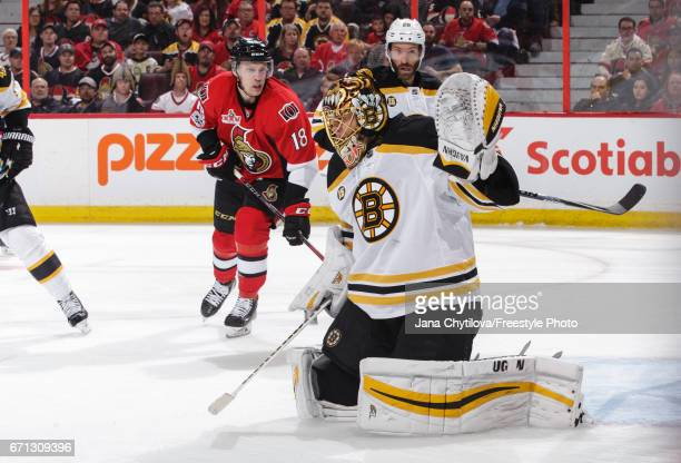 Tuukka Rask of the Boston Bruins makes a save as teammate Dominic Moore defends against Ryan Dzingel of the Ottawa Senators in the second period in...