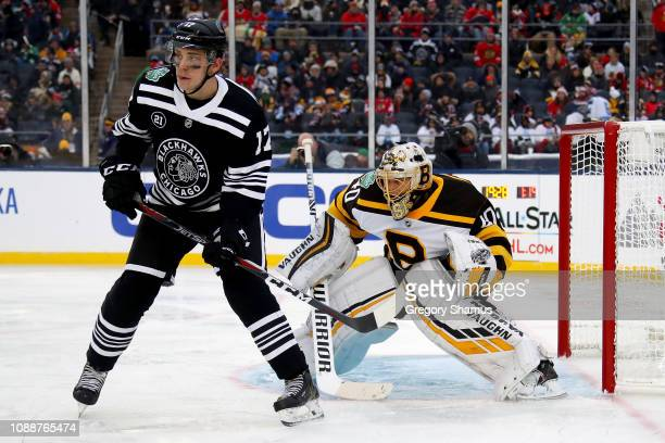 Tuukka Rask of the Boston Bruins plays goalie next to Dylan Strome of the Chicago Blackhawks in the third period during the 2019 Bridgestone NHL...