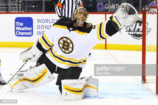 Tuukka Rask of the Boston Bruins reaches for the puck during the third period against the New York Islanders at Barclays Center on January 2 2018 in...