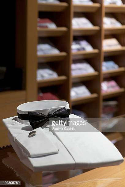 A tuxedo shirt and bow tie in a menswear store