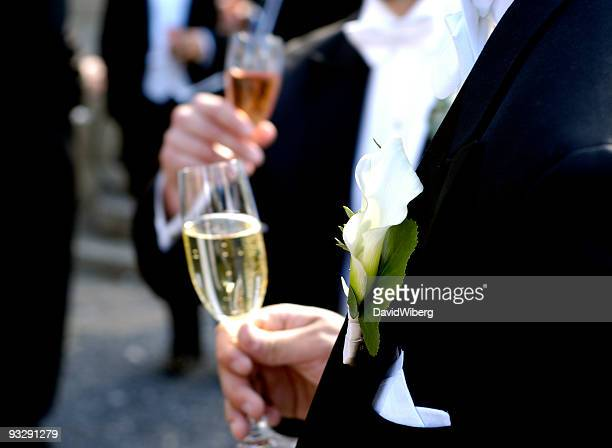 Tuxedo-clad men drinking champagne and mingle at a wedding event