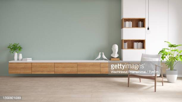 tv cabinet and display with on wood flooring and pastel green wall, minimalist and vintage interior - salon fotografías e imágenes de stock