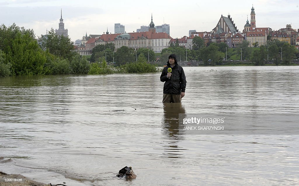 A Tv journalist reports the situation in Warsaw standing in high water at Wisla river in Warsaw on May 20,2010.Flash floods caused by days of heavy rainfall have hit parts of central Europe, killing at least seven people, disrupting power supplies and forcing thousands of people from their homes. Southern Poland, parts of the Czech Republic and Slovakia and northern Hungary are among the worst affected regions