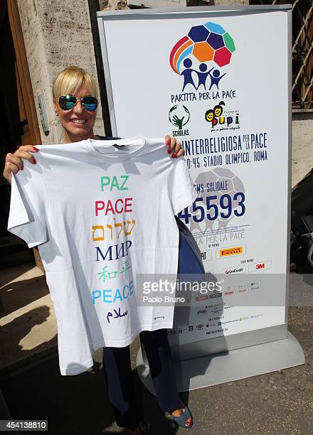 Tv Presenter Antonella Clerici holds a tshirt with the written ' Peace' before the 'Interreligious match for Peace' press conference on August 25...