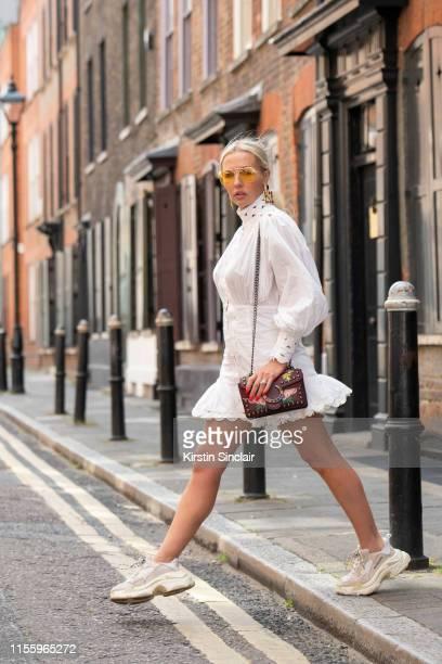 Tv Presenter Naomi Isted wears Balenciaga trainers, Amschela bag, Siiren Suhreen dress and yellow sunglasses during London Fashion Week Men's June...