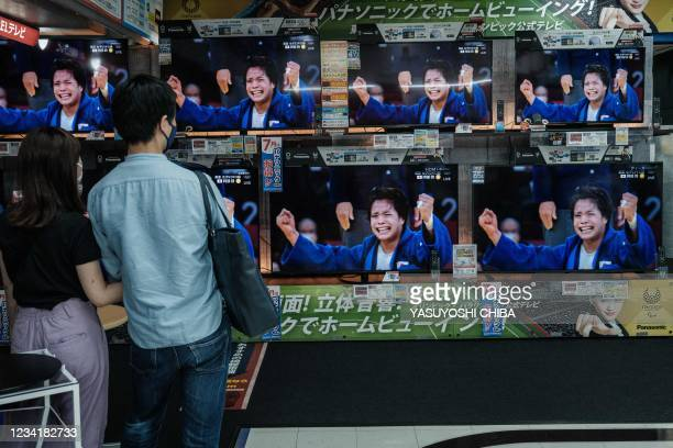 TVs display Japan's Uta Abe after winning the judo women's -52kg final bout against France's Amandine Buchard during the Tokyo 2020 Olympic Games at...