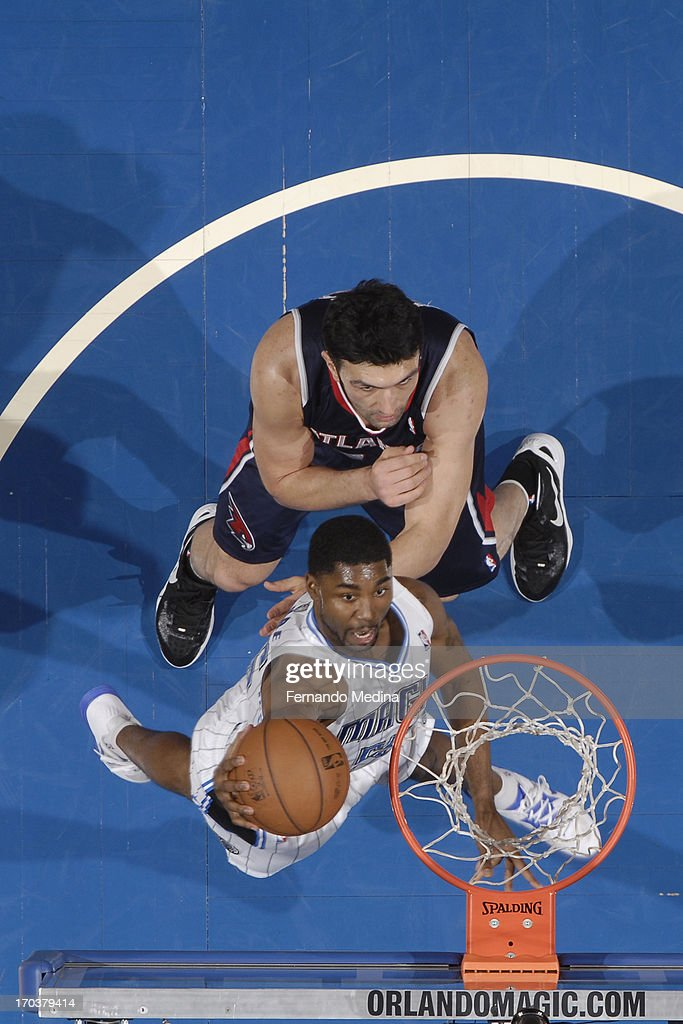 E'Twaun Moore #55 of the Orlando Magic drives to the basket against Zaza Pachulia #27 of the Atlanta Hawks on February 13, 2013 at Amway Center in Orlando, Florida.
