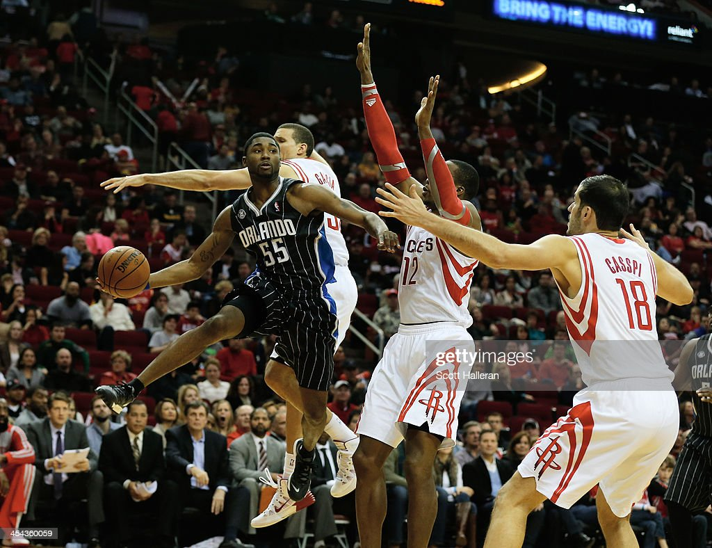 E'Twaun Moore #55 of the Orlando Magic looks to pass beyond Francisco Garcia, Dwight Howard and Omri Casspi #18 of the Houston Rockets at Toyota Center on December 8, 2013 in Houston, Texas.