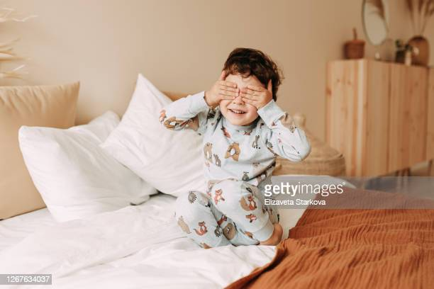 tween boy in pajamas playing on bed at cozy home - school cane stock pictures, royalty-free photos & images