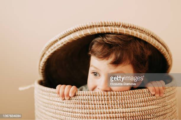 tween boy playing in wicker basket at home - school cane stock pictures, royalty-free photos & images