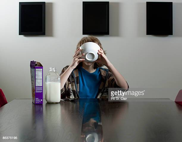 tween drinking milk cereal bowl - viso nascosto foto e immagini stock
