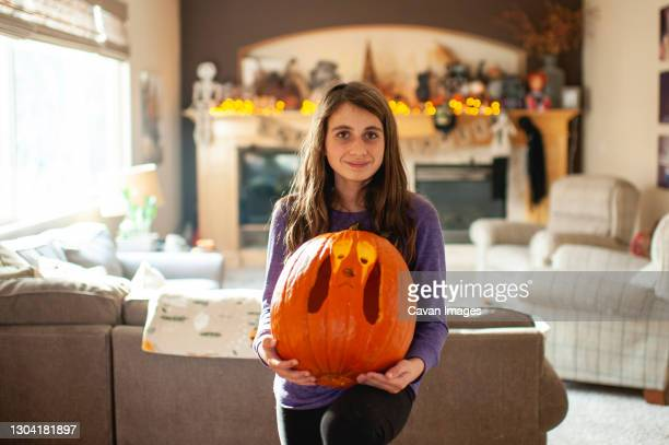 tween girl 10-12 years old holds up carved pumpkin in living room - 10 11 years stock pictures, royalty-free photos & images