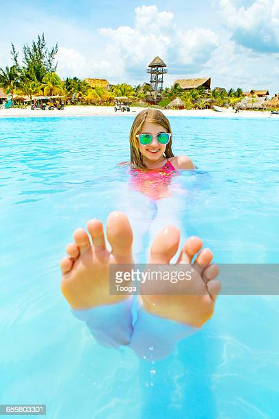 Tween girl floating beautiful blue ocean
