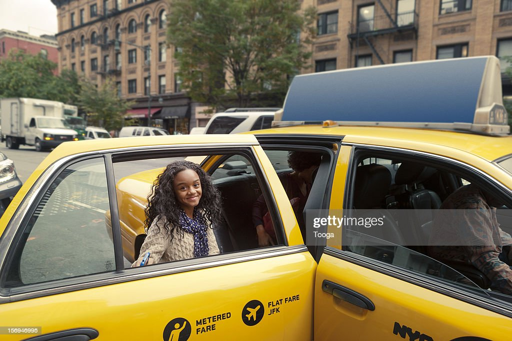 Tween girl getting into cab and smiling : Foto de stock