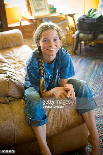 'tween' girl in jeans sitting on couch