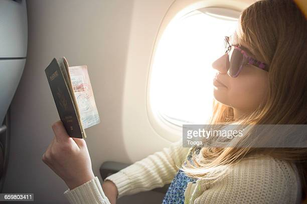 Tween girl looking at stamps on passport