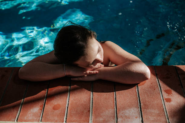 Tween girl resting head on the side of a swimming pool