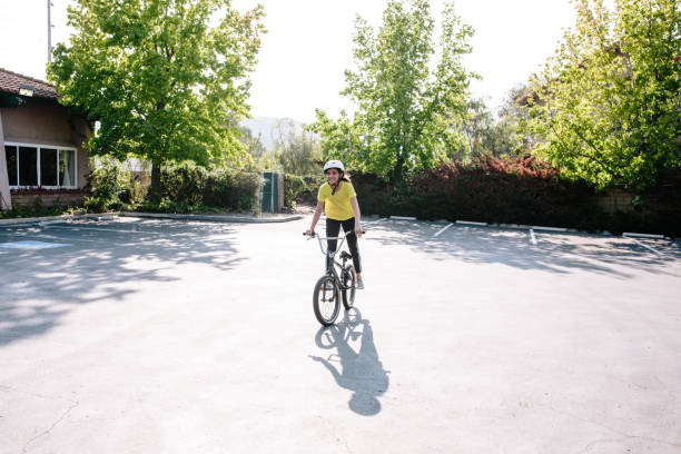 Tween girl stands on the pedals of her bike while smiling