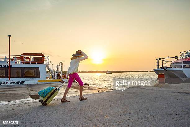 Tween girl with suitcase walking on dock