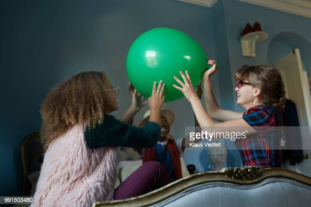 Tween girlfriends playing with giant balloon, at home