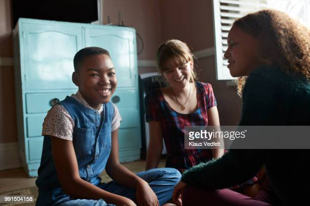 Tween girls laughing together in their room